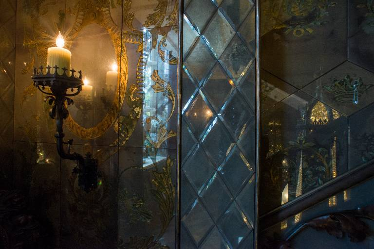 Mirrored walling in etched gilded bevelled and antiqued mirror glass with wrought iron candelabra, 2012