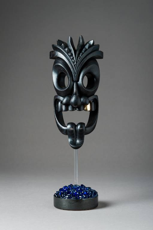 A tiki inspired carved wood sculpture in ebonised ash